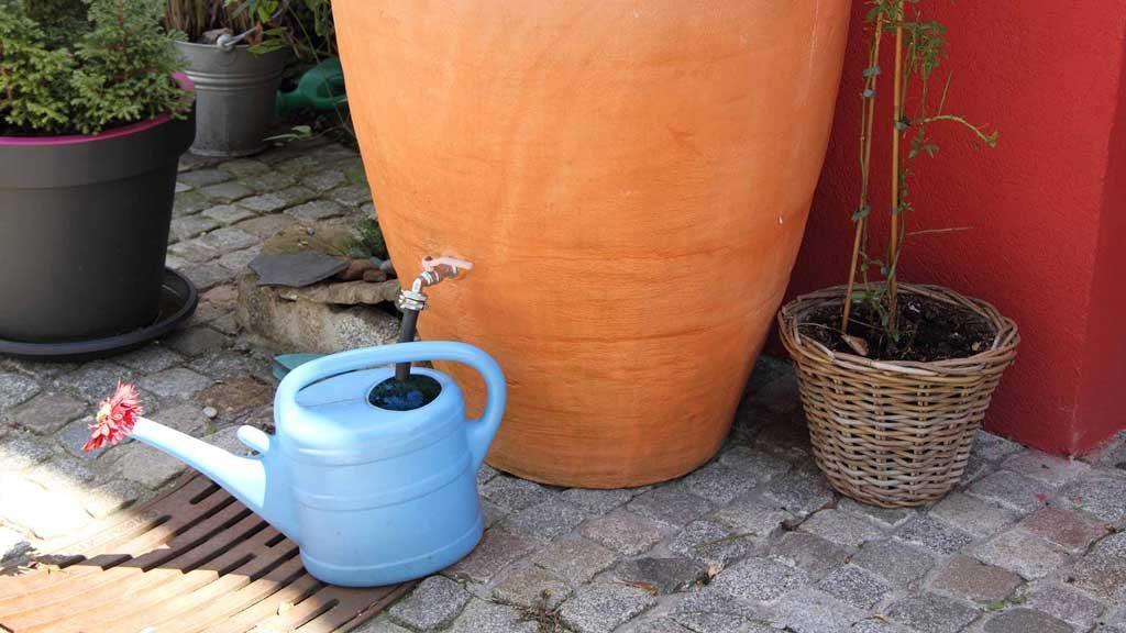 Garten-Fibel - einer Regentonne, die wie eine Terrakotta-Amphore aussieht, wird Wasser entnommen