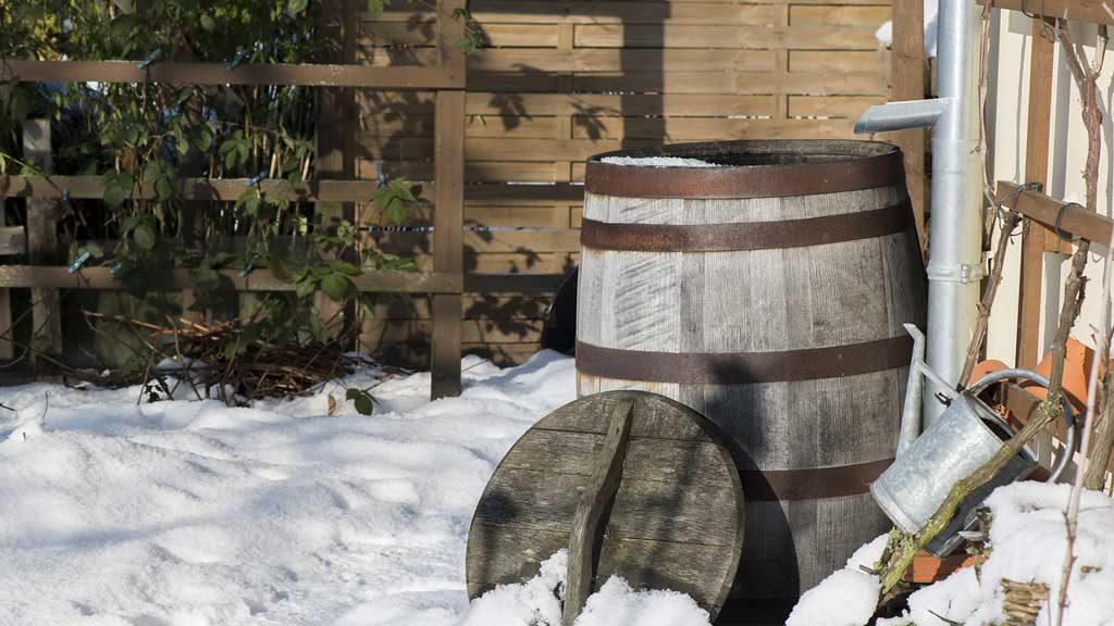 Garten-Fibel - eine Regentonne, die wie ein ehemaliges Weinfass aussieht an der Hauswand im Winter